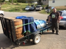 Zach from Blue Ghost Brewing Company picking up fermenters and whiskey barrels